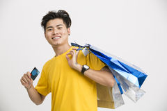 Happy smart  Indian man standing with credit card with shopping bag Royalty Free Stock Photo