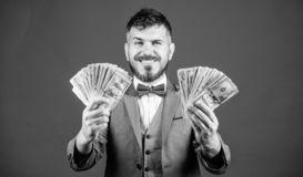 Happy with smart investments. Currency broker with bundle of money. Making money with his business. Business startup. Loan. Bearded man holding cash money. Rich stock image