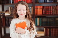 Happy smart schoolgirl reading books in library or at home. Kids early learning and education concept royalty free stock photo