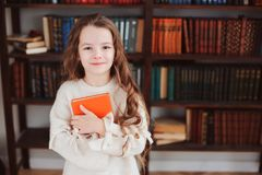 Happy smart schoolgirl reading books in library or at home. Kids early learning and education concept royalty free stock photos