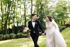 Happy smile bride and groom look at each other and running in the green garden. Wedding in the summer in the park. Happy royalty free stock photos