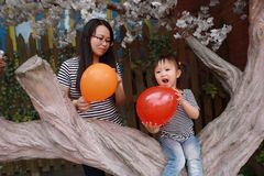 Happy smile child with mother mom and daughter play balloon outdoor family parental activity joyful childhood summer. A little Asian Chinese girl, have fun and stock image