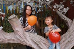 Happy smile child with mother mom and daughter play balloon outdoor family parental activity joyful childhood summer. A little Asian Chinese girl, have fun and stock photo