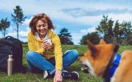 Happy smile girl holding in hands cup drink playing with red japanese dog shiba inu on green grass in outdoors nature park, young stock photography