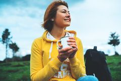 Happy smile girl holding in hands cup of hot tea on green grass in outdoors nature park, beautiful young woman hipster enjoy drink royalty free stock images