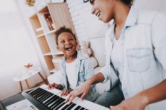 Happy and Smile Girl Play on Piano with Mother. stock photo