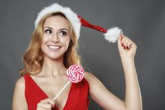 Happy smile girl wearing a santa suit holding a candy for christ Stock Images