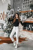 Happy smile woman Holding Hands New Year`s Balloons and jumping in decorated room with Christmas tree and fireplace royalty free stock images