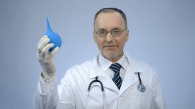 Happy smiled proctology doctor showing rubber syringe and looking at camera. Stock photo stock image