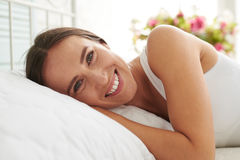 Happy smiled woman lying on the bed in the morning Stock Images