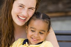 Happy Smiles. Freckled young beautiful brunette woman with young big brown-eyed beautiful african american boy child both smiling Stock Images
