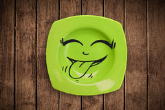 Happy smiley cartoon face on colorful dish plate. And grungy background Royalty Free Stock Photos