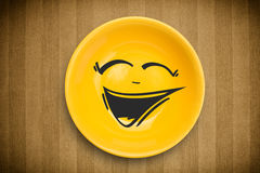 Happy smiley cartoon face on colorful dish plate. And grungy background Stock Photo