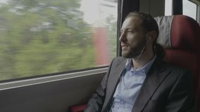 Happy smiley corporate man commuting on work by train having fun listening favorite music on headphones -. Happy smiley corporate man commuting on work by train stock footage