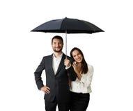Happy smiley couple under black umbrella. Isolated on white background Stock Photo