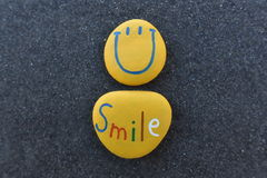 Happy Smiley Emoticon design with colored stones over black volcanic sand Royalty Free Stock Images