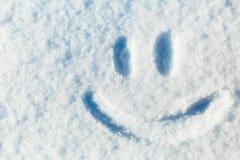 Happy smiley emoticon face in snow, winter season joy concept Stock Images
