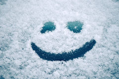 Happy smiley emoticon face in snow Stock Images