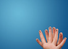Happy smiley face fingers looking at empty blue background copy Royalty Free Stock Image