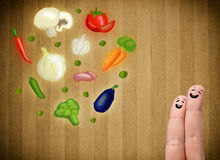 Happy smiley face fingers looking at illustration of colorful he. Happy smiley face fingers cheerfully looking at illustration of colorful healthy vegetables Stock Photos