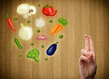 Happy smiley face fingers looking at illustration of colorful he. Happy smiley face fingers cheerfully looking at illustration of colorful healthy vegetables Stock Images