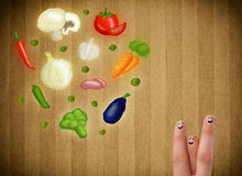 Happy smiley face fingers looking at illustration of colorful he. Happy smiley face fingers cheerfully looking at illustration of colorful healthy vegetables Stock Photo