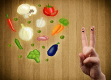 Happy smiley face fingers looking at illustration of colorful he. Happy smiley face fingers cheerfully looking at illustration of colorful healthy vegetables Royalty Free Stock Image