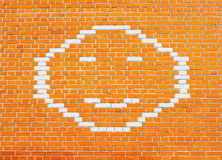 Happy Smiley Face on orange brick wall Stock Photo