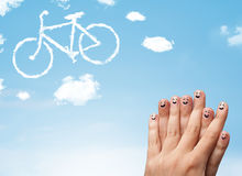 Happy smiley fingers looking at a bicycle shapeed cloud Stock Images