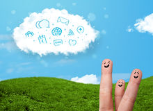 Happy smiley fingers looking at cloud with blue social icons and. Happy cheerful smiley fingers looking at cloud with blue social icons and smybols Royalty Free Stock Image