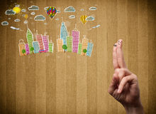 Happy smiley fingers looking at colorful handrawn cityscape Stock Photos