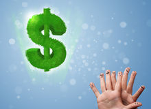 Happy smiley fingers looking at green leaf dollar sign Stock Images