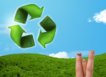 Happy smiley fingers looking at green leaf recycle sign Royalty Free Stock Image