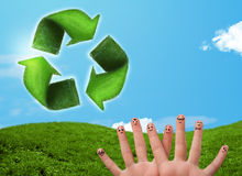 Happy smiley fingers looking at green leaf recycle sign Stock Photography