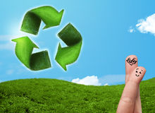Happy smiley fingers looking at green leaf recycle sign Royalty Free Stock Photography