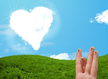 Happy smiley fingers looking at heart shaped cloud Stock Photos