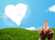 Happy smiley fingers looking at heart shaped cloud Stock Image