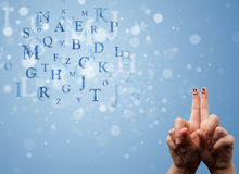 Happy smiley fingers looking at mixture of bokeh letters Royalty Free Stock Image