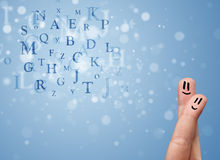 Happy smiley fingers looking at mixture of bokeh letters Stock Photos