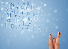 Happy smiley fingers looking at mixture of bokeh letters Royalty Free Stock Photo