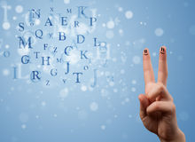 Happy smiley fingers looking at mixture of bokeh letters Stock Photo