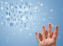 Happy smiley fingers looking at mixture of bokeh letters Royalty Free Stock Images