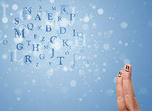 Happy smiley fingers looking at mixture of bokeh letters Stock Images