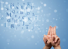 Happy smiley fingers looking at mixture of bokeh letters. Happy cheerful smiley fingers looking at mixture of bokeh letters Royalty Free Stock Image