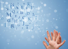 Happy smiley fingers looking at mixture of bokeh letters Royalty Free Stock Photography