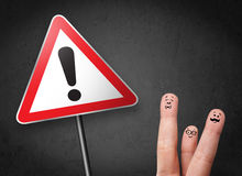 Happy smiley fingers looking at triangle warning sign with excla Stock Photo