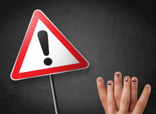 Happy smiley fingers looking at triangle warning sign with excla Stock Photography