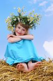 Happy smiley girl with camomile wreath. Outdoors over blue sky on straw haystack Stock Image