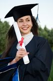 Happy smiley graduate girl. Young smiley graduate girl student in gown with diploma outdoors Stock Photos