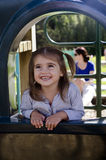 Happy smiley little girl. In the playground while her mother watching her daughter Royalty Free Stock Image